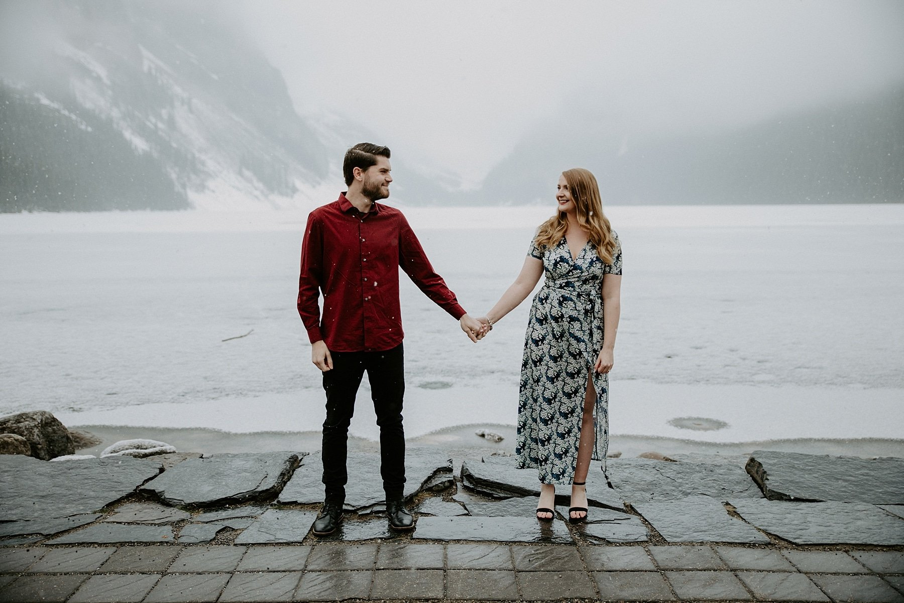 engaged couple holding hands in front of Lake Louise