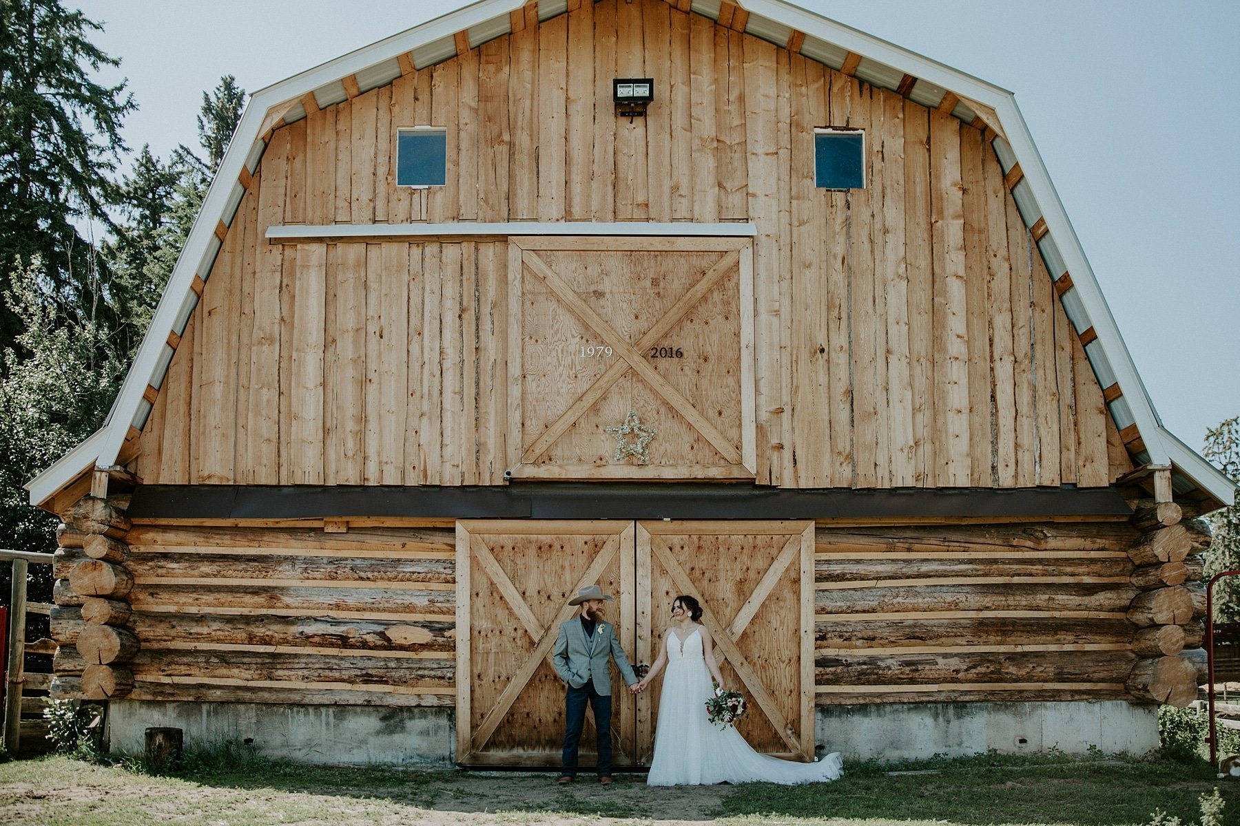 Country wedding with bride and groom standing in front of barn